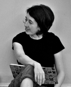 A black and white photo of a woman in a t-shirt and pants sitting on the floor with a book or journal.