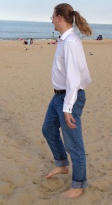 A white man with long blond hair in jeans and a white shirt walks barefoot on the beach.