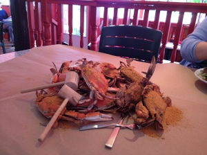 A large pile of boiled hard-shelled crabs on a paper-covered table.