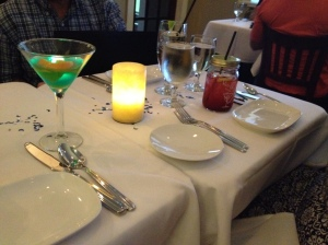 A set table with a martini glass in which a plastic square lit by a green LED is floating.
